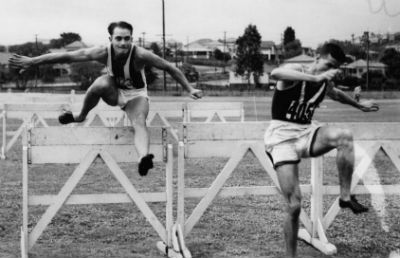 B&W photo of hurdlers jumping a fence for fitness