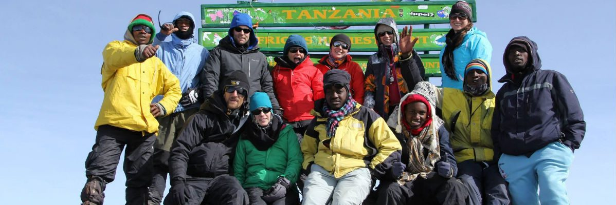 Guides and trekkers posing in front of the old metal Uhuru Peak signboard