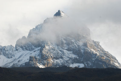 The triangular Mawenzi summit, half obscured by cloud and frosted with snow, as seen from the Rongai Route on the way to Kikelewa Camp