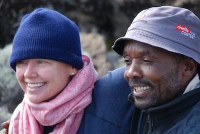 Female trekker with arm round shoulder of guide Alex Minja