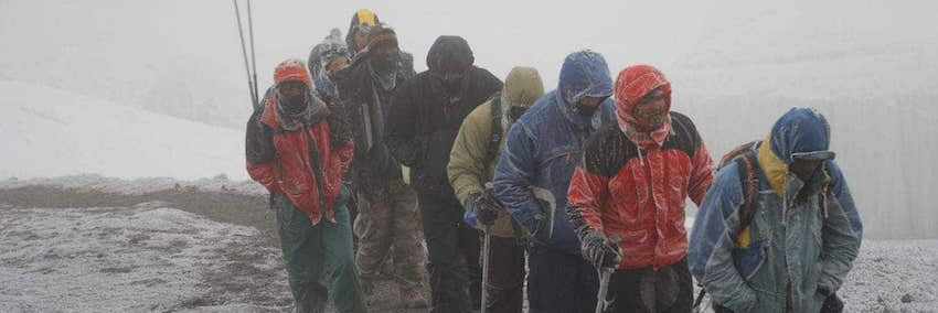 Line of trekkers struggling through the snows of Kilimanjaro -prehaps not the best time to climb Kilimanjaro