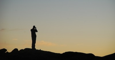 Silhouette of photographer at dusk at Mawenzi Tarn Hut