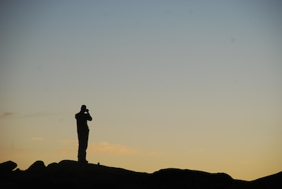 Silhouette of photographer at dusk at Mawenzi Tarn Hut