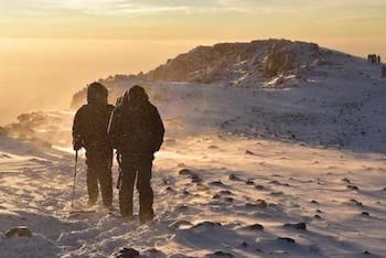 Silhouette of two men walking on the summit of Kilimanjaro in a blizzard