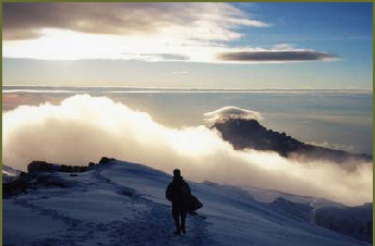 Walking through the snow near the summit at dawn, with Mawenzi in the distance