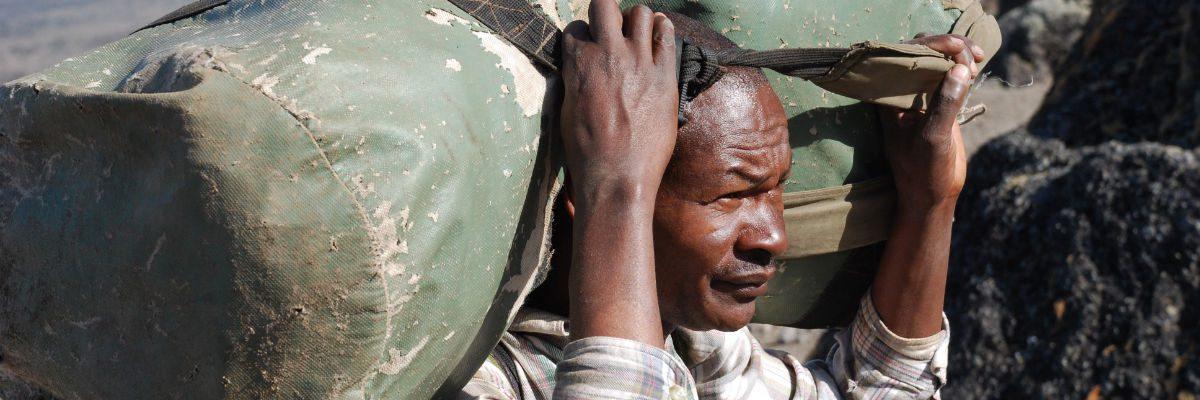 Elderly porter carrying large green kit bag on his shoulders