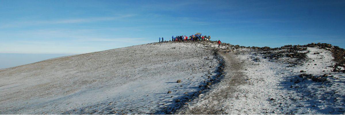 Path snaking towards a crowd surrounding the signboard at Uhuru Peak