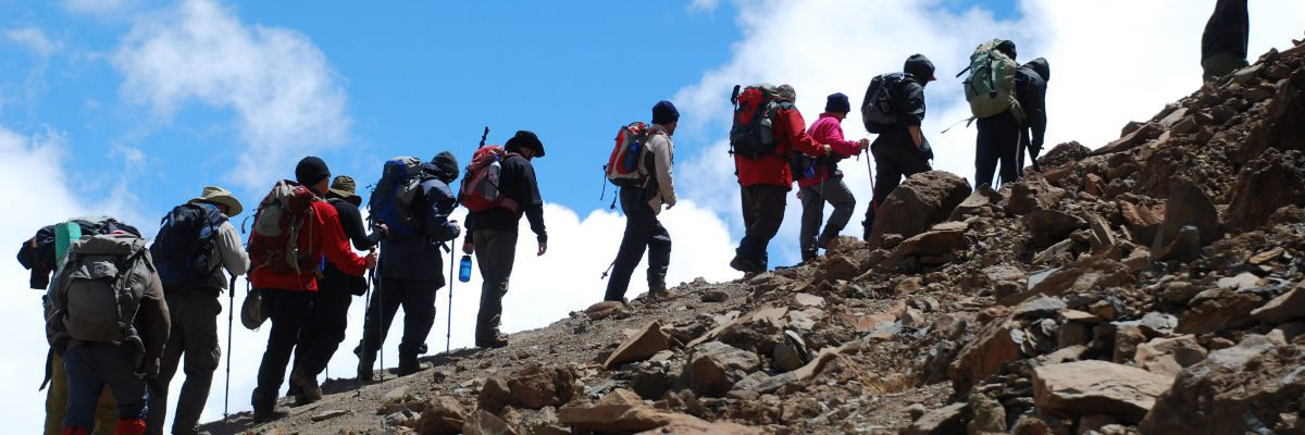 Low-level shot of a line of trekkers edging up the slopes of Kibo