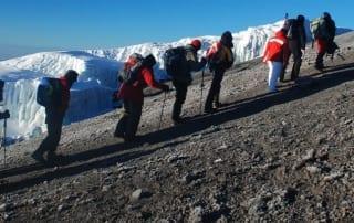 A line of trekkers trudging towards Uhuru Peak past Rebmann Glacier