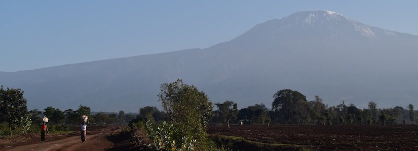View of Kilimanjaro with two ladies walking along a path - for those who booked after they've arrived in Tanzania