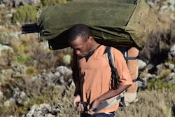 Porter in an orange T-shirt on the Machame Route with a bag on his shoulders