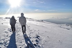 Two men trudging through the snow at the top of Kilimanjaro
