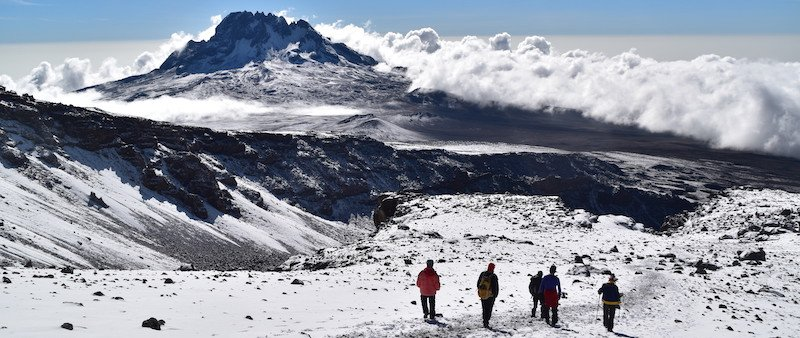 Strolling in the snow on Kili with Mawenzi in the background for how to make your kilimanjaro trek cheaper