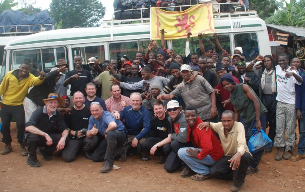 Group of Scottish climbers celebrating in front of their bus at the end of a trek